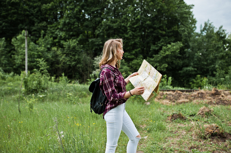 Portrait of a beautiful blond girl in tartan shirt walking with a map in the countryside.