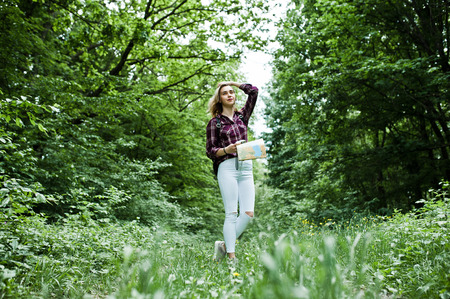 Portrait of a young beautiful blond woman in tartan shirt holding a map in the forest.