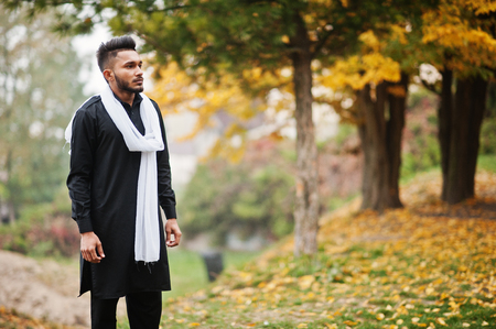 Indian stylish man in black traditional clothes with white scarf posed outdoor against yellow autumn leaves tree.