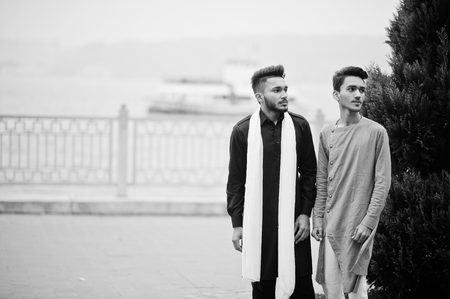 Two indian stylish mans friends in traditional clothes posed outdoor against steamboat on sea.