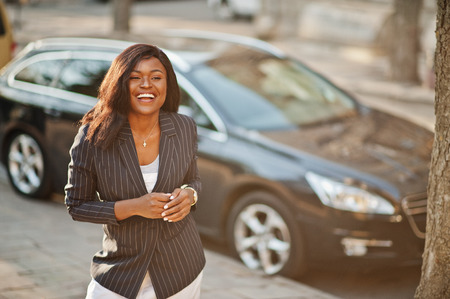 Success stylish african american woman in jacket against black car. Stockfoto