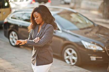 Success stylish african american woman in jacket against black car looking at her watches.