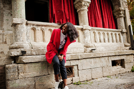 Stylish african american woman in red coat posed against old columns. Stock Photo
