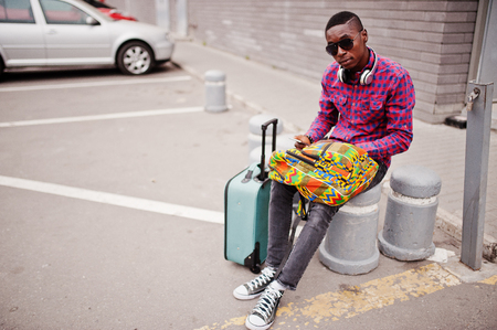 African american man in checkered shirt, sunglasses and earphones with suitcase and backpack. Black man traveler holding mobile phone at hand. Foto de archivo