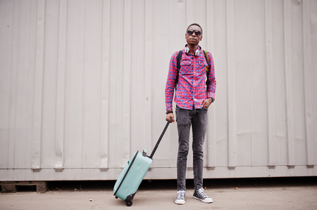 African american man in checkered shirt, sunglasses and earphones with suitcase and backpack. Black man traveler against wall.