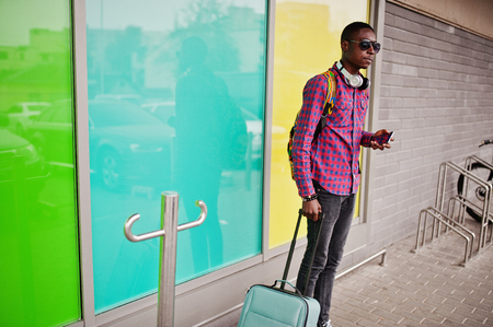 African american man in checkered shirt, sunglasses and jeans with suitcase and backpack. Black man traveler.