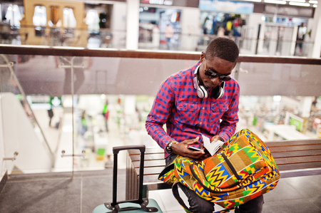 African american man in checkered shirt, sunglasses and jeans with suitcase and backpack. Black man traveler checked his passport on duty free.