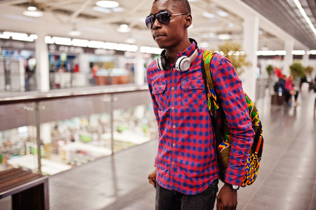 African american man in checkered shirt, sunglasses and jeans with suitcase and backpack. Black man traveler on duty free.