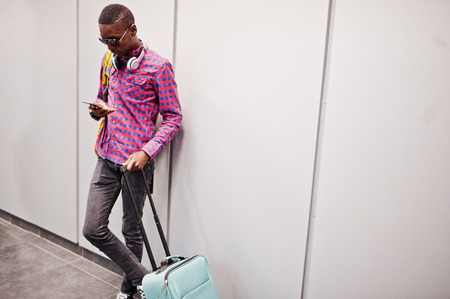 African american man in checkered shirt, sunglasses and jeans with suitcase and backpack. Black man traveler against gray wall. Foto de archivo