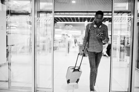 African american man in checkered shirt, with suitcase and backpack. Black man traveler on duty free.