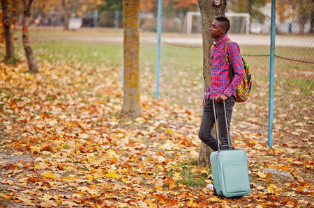 African american man in checkered shirt, with suitcase and backpack. Black man traveler at autumn park. Foto de archivo