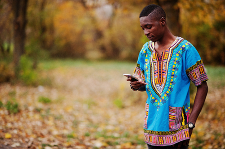 African man in africa traditional shirt on autumn park. 스톡 콘텐츠