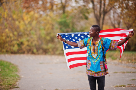 African man in africa traditional shirt on autumn park with USA flag.