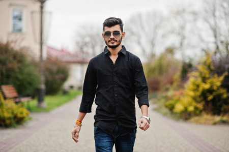 Indian stylish man at black shirt and sunglasses posed outdoor.
