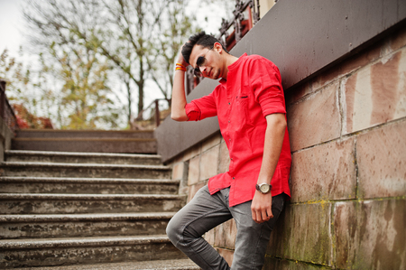 Indian man at red shirt and sunglasses posed outdoor. Stock Photo