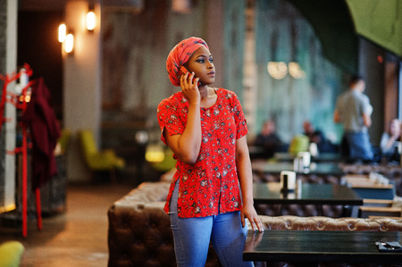 Stylish african woman in red shirt and hat posed indoor cafe and speaking mobile phone. Imagens