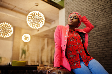 Stylish african woman in red shirt, jacket and hat posed indoor cafe. Stock Photo