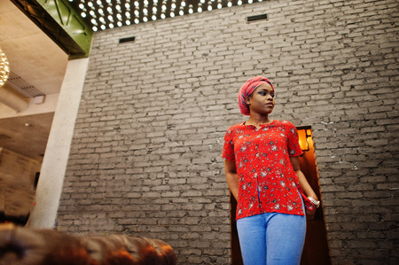 Stylish african woman in red shirt and hat posed against brick wall. Imagens