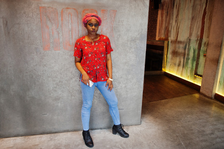 Stylish african woman in red shirt and hat posed indoor cafe.