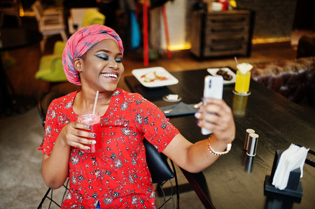 Stylish african woman in red shirt and hat posed indoor cafe, drinking strawberry lemonade and making selfie on phone.