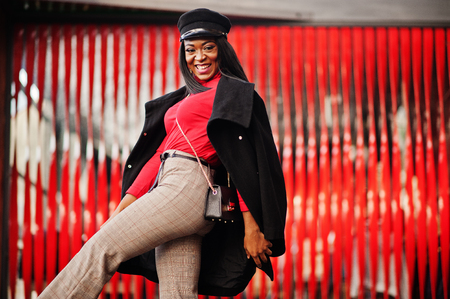 African american fashion girl in coat and newsboy cap posed at street against red background. Imagens