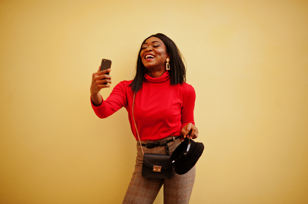 African american fashion girl with newsboy cap posed against yellow background with mobile phone.