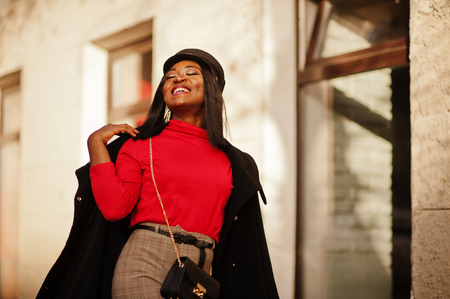 African american fashion girl in coat and newsboy cap posed at street. Imagens