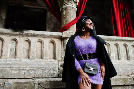 African american woman at violet dress and cap posed outdoor against old column with red curtains.