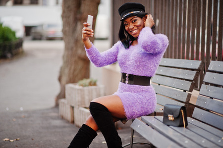 African american woman at violet dress and cap posed outdoor, sitting on bench and making selfie on phone.