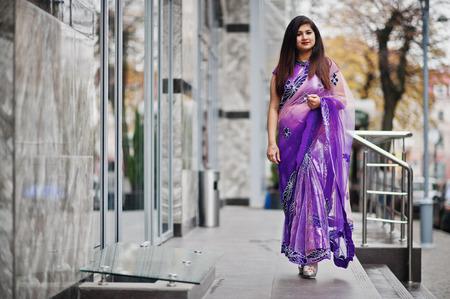 Indian hindu girl at traditional violet saree posed at street.