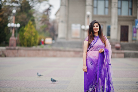 Indian hindu girl at traditional violet saree posed at street against doves.