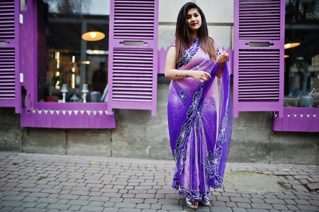 Indian hindu girl at traditional violet saree posed at street against purple windows.