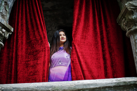 Indian hindu girl at traditional violet saree posed at  street against old house with red curtains. Stock Photo