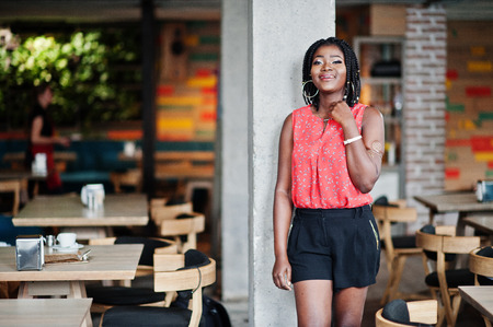 Attractive african american woman with short dreads posed on cafe.