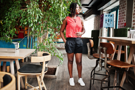 Attractive african american girl posed at cafe against tree. Imagens