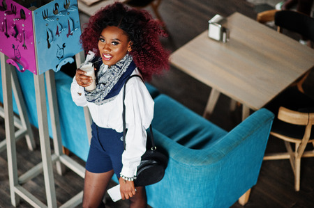 Attractive african american curly girl in white blouse and blue shorts posed at cafe with latte and mobile phone at hand. View from above. Stock fotó - 112020743