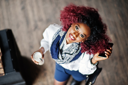 Attractive african american curly girl in white blouse and blue shorts posed at cafe with latte and mobile phone at hand. View from above. Imagens