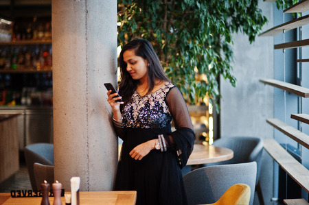 Pretty indian girl in black saree dress posed at restaurant with mobile phone at hand.