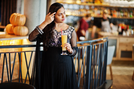 Pretty indian girl in black saree dress posed at restaurant with orange juice at hand.