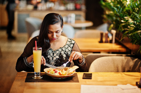 Pretty indian girl in black saree dress posed at restaurant, sitting at table with juice and salad. Imagens
