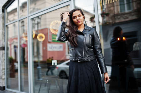 Pretty indian girl in black saree dress and leather jacket posed outdoor at street.