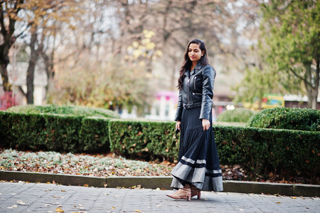 Pretty indian girl in black saree dress and leather jacket posed outdoor at autumn street.