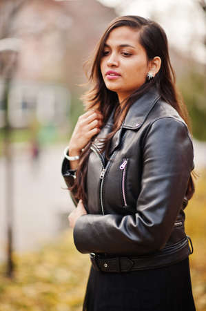Close up portrait of pretty indian girl in black saree dress and leather jacket posed outdoor at autumn street. Stock Photo