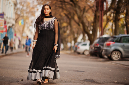 Pretty indian girl in black saree dress posed outdoor at autumn street.