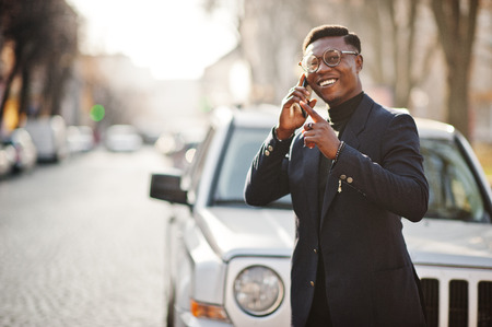 Amazingly looking african american man wear at blue blazer with brooch, black turtleneck and glasses posed at street. Fashionable black guy speaking on phone against car.