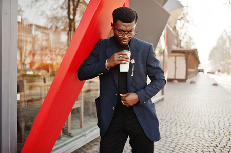 Amazingly looking african american man wear at blue blazer with brooch, black turtleneck and glasses posed at street. Fashionable black guy with cup of coffee.