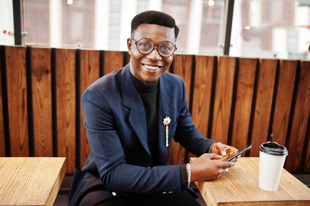 Amazingly looking african american man wear at blue blazer with brooch, black turtleneck and glasses posed at street. Fashionable black guy with cup of coffe looking at his phone.