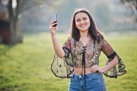 Pretty latino model girl from Ecuador wear on jeans posed at street with mobile phone. Banque d'images