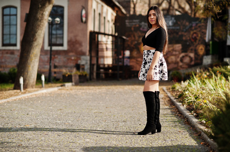 Pretty latino model girl from Ecuador wear on black tops and skirt posed at street.