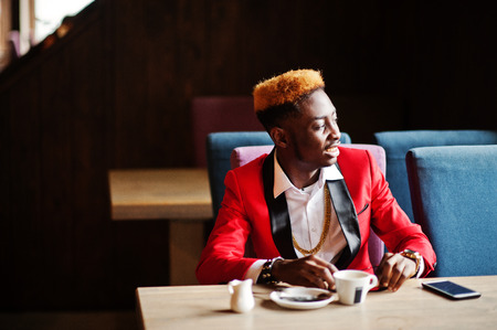 Fashion african american man model at red suit, with highlights hair sitting at cafe with coffee.